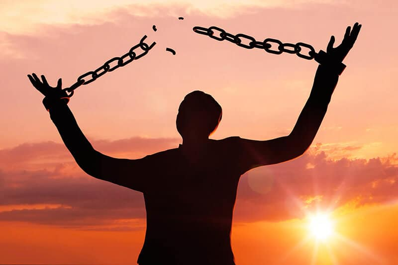 Person vor Sonnenuntergang gesprengte Ketten durch Hypnose